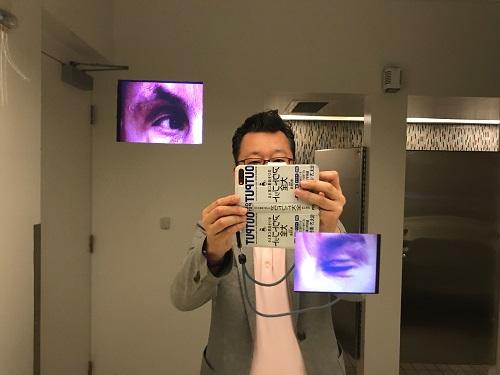 ミュージアムホテルのトイレ。トイレの手洗いのガラスに空いた小窓から人が覗いている!